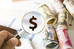 Hand holding magnifier glass for searching US dollar sign and financial report.Value investor find the best stock on market