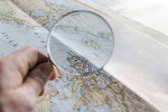 Hand holding magnifier and looking at map, focus map Stock Images