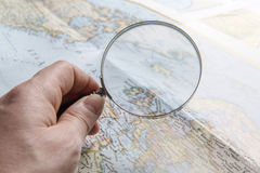Hand holding magnifier and looking at map; hand focused Stock Image