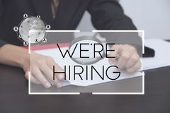 Hand holding magnifier with we`re hiring text. concept employmen. T recruitment hiring Stock Photography