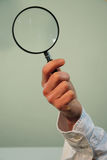 Hand holding magnifying glass. A closeup view of a hand holding a large magnifying glass used to visually enlarge or amplify size stock images