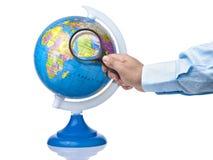 Hand holding magnifying glass on Arabian peninsula on globe isolated. On white Royalty Free Stock Photos