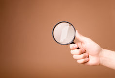 Hand holding magnifying glass on the beige background Stock Images