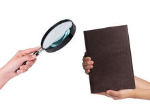 Hand  holding a magnifying glass and a book  on white background Royalty Free Stock Images