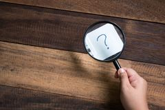 Hand holding magnifying glass focusing on question mark. Mystery and search concept Stock Images
