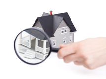 Hand holding magnifying glass in front of the home Royalty Free Stock Photos