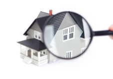 Hand holding magnifying glass in front of house Stock Photo