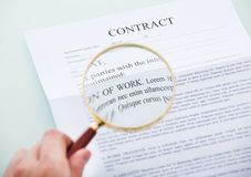 Hand holding magnifying glass over contract Stock Image