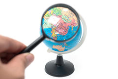 Hand holding magnifying glass over earth globe Stock Photo