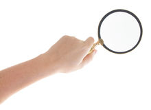 Hand holding a magnifying glass. Someones hand holding a magnifying glass isolated on white background Royalty Free Stock Photography