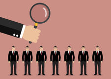 Hand holding magnifying glass to find employee. Recruitment concept Royalty Free Stock Photos
