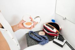 Hand holding makeup cosmetic brown power. Close up of woman hand holding makeup brush brown power. Female carrying blush box to make up in toilet or restroom Royalty Free Stock Photo