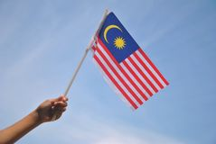 Hand holding Malaysia Flag. Independence Day / Merdeka day concept - Hand holding Malaysia Flag and waving it into the sky Royalty Free Stock Image