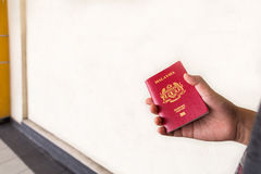 Hand holding Malaysia international passport against wall backgr Royalty Free Stock Photos