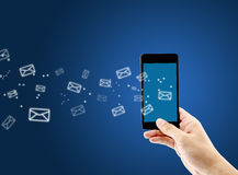 Hand holding man check and sending message with email in a phone. Hand holding man check and sending message with email in a phone on blue background Stock Image