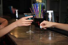 A hand is holding a martini glass on a bar in a nightclub, filled with turquoise cocktails. With blurred background stock image