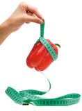 Hand holding measuring tape tied around paprika. Hand holding measuring tape tied around paprika Royalty Free Stock Photography