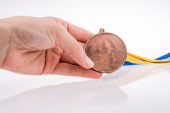 Hand holding medal. Hand holding a medal with blue and yellow ribbon Royalty Free Stock Photos