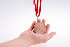 Hand holding medal. Hand holding a medal with red and white ribbon Stock Photography