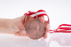 Hand holding medal. Hand holding a medal with red and white ribbon Royalty Free Stock Photo