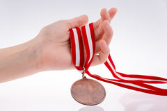 Hand holding medal. Hand holding a medal with red and white ribbon Royalty Free Stock Image