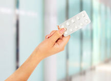 Hand holding medical drugs - full silver leaflet of white pills Royalty Free Stock Images
