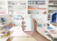 Hand holding medicine bottle. With blur some shelves of drug in the pharmacy drugstore Royalty Free Stock Photography