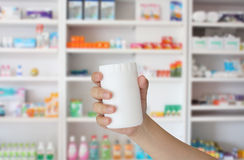 Hand holding medicine bottle. With blur some shelves of drug in the pharmacy drugstore Royalty Free Stock Image