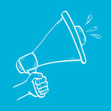 Hand holding megaphone on blue background. Royalty Free Stock Photo