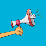Hand holding megaphone on blue background. Royalty Free Stock Photos