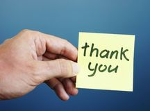 Hand is holding memo stick with sign Thank you. Hand holding memo stick with sign Thank you royalty free stock photos