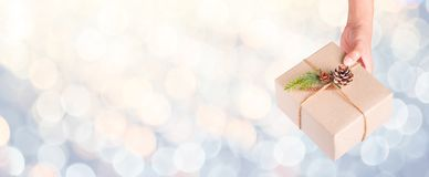 Hand holding merry christmas present diy box with pastel yellow stock photography