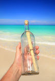 Hand holding message in a bottle Royalty Free Stock Photography