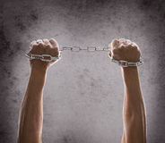 Hand holding metal chain with strong power on grungy background Royalty Free Stock Photos