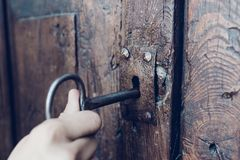 Hand holding metal vintage key to unlocking old secret wooden do. Or, film tone color Royalty Free Stock Photography