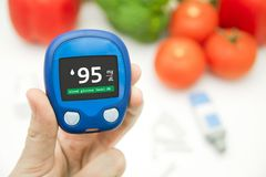 Hand holding meter. Diabetes doing glucose level test. Royalty Free Stock Photo