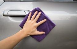 Hand holding microfiber cloth polishing gray car Royalty Free Stock Images