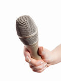 Hand holding microphone. Woman's hand holding microphone isolated on white Royalty Free Stock Photography