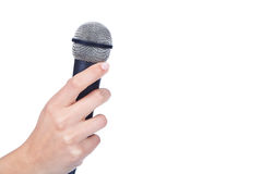 Hand holding a microphone. Female hand holding a microphone stock photos