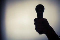 Hand holding a microphone. Close up shot of a silhouette of a hand holding a microphone stock photo