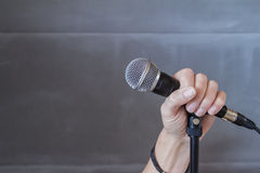 Hand holding a microphone in a conceptual image Royalty Free Stock Image