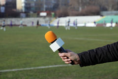 Hand holding microphone for interview. During a football mach Stock Images
