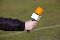 Hand holding microphone for interview during a football mach Stock Images