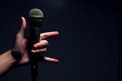 Hand holding microphone making Rock symbol Stock Photos