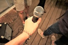 Hand holding microphone at party. Karaoke party with amp, legs dancing on deck.  Woman`s hand with silver watch holding silver microphone royalty free stock photography
