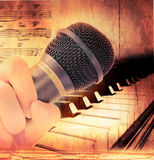 Hand holding microphone and piano Stock Photos