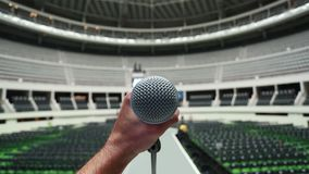 Hand holding a microphone during rehearsal and sound-check before a show at the venue. stock video