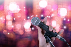 Hand holding microphone on stand with bokeh . Hand holding microphone on stand with bokeh glow blurred background. Singer on karaoke stage party stock images