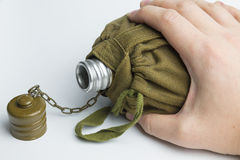 Hand holding military flask on white background. Royalty Free Stock Images