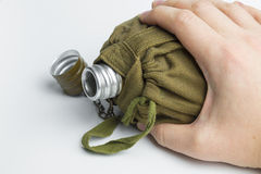 Hand holding military flask on white background. Royalty Free Stock Photo